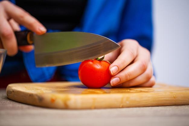 De close-up van vrouw snijdt tomaat voor verse salade Premium Foto