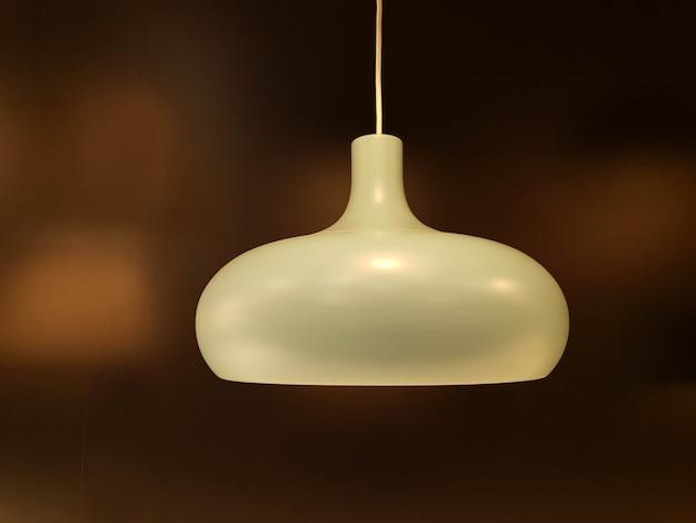 De close-up verfraait de witte lamp van het huisplafond op onscherpe bruine achtergrond. Premium Foto