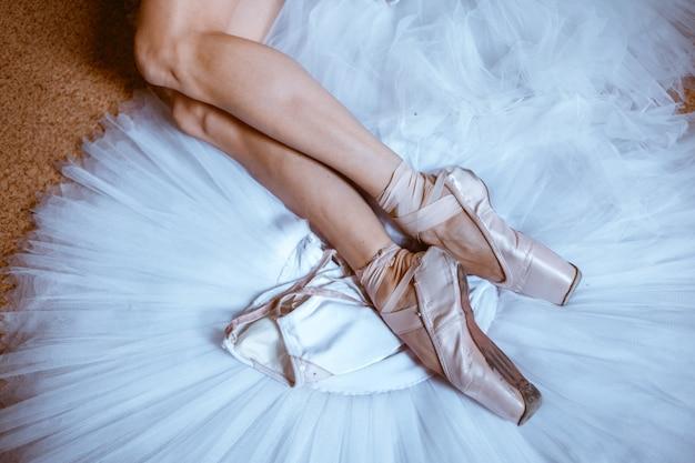 De close-up voeten van jonge ballerina in pointe-schoenen Gratis Foto