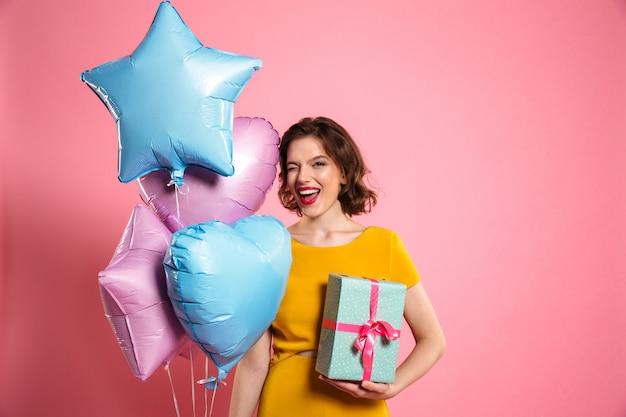 De close-upfoto van speels feestvarken met rode lippen knipoogt één oog terwijl de giftdoos en ballons houden Gratis Foto