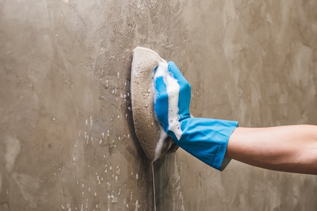 De close-uphand die blauwe rubberhandschoenen draagt gebruikt spons het schoonmaken op de concrete muur. Premium Foto