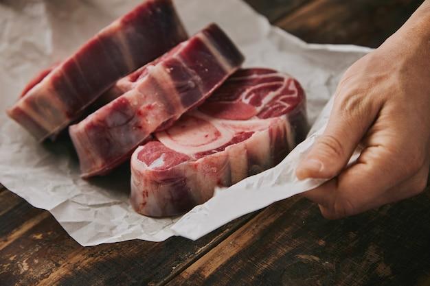 De close-uphand houdt wit kraftpapier vast met drie ruwe grote beenlapjes vlees met been erop, alles op oude houten geborstelde lijst Gratis Foto