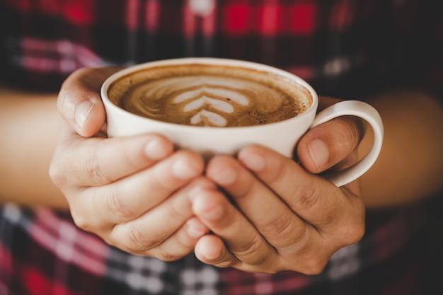 De close-uphand van wijfje die een koffiekop in de koffie houden voegt de toon van de filter retro kleur toe Gratis Foto