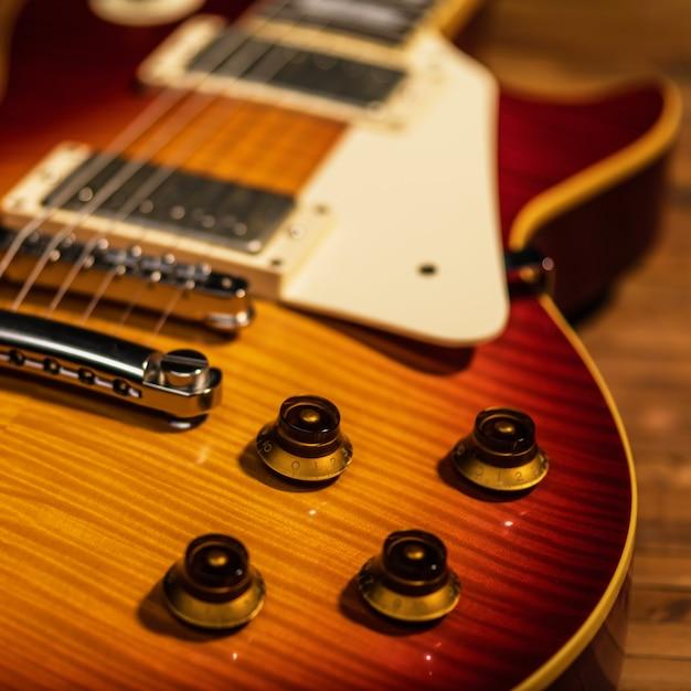 De close-upmening van het elektrische gitaarlichaam is op de houten vloer Gratis Foto