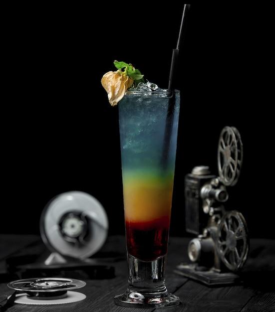 De cocktail van de kleurenalcohol wiith bloem en zwarte pijp. Gratis Foto