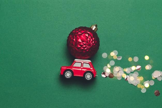 De creatieve kerstmissamenstelling met een rode stuk speelgoed auto met een kerstmisbal op de kap en fonkelt snoep op een groene achtergrond met compise. platliggend, minimale stijl Premium Foto
