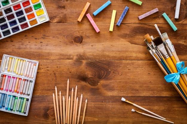 De creatieve toebehoren van het kunstwerk op bruine houten vlakke achtergrond, leggen, exemplaarruimte Premium Foto