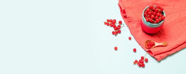 De creatieve zomer van rode rijpe bessen in een blauwe kop en met een houten lepel op een blauwe achtergrond Premium Foto