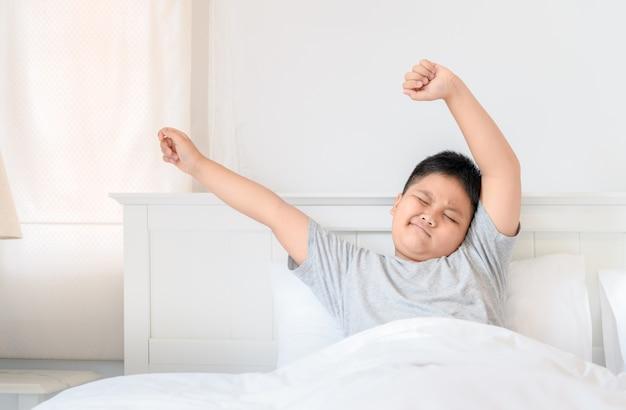 De dikke jongen van obses zit op bed en rekt zich uit. Premium Foto