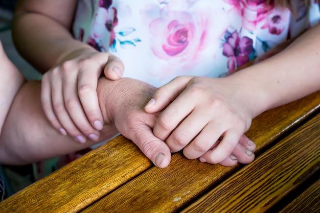 De dochter houdt de hand van de moeder in haar handen Premium Foto