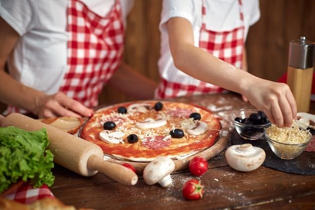 De dochter kokende pizza en het glimlachen van het moederonderwijs Premium Foto