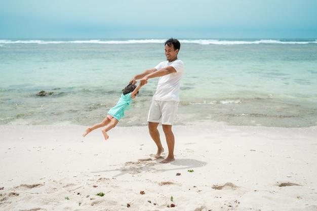 De dochterhanden van de vaderholding wanneer het spelen van schommeling op het strand roteert Premium Foto
