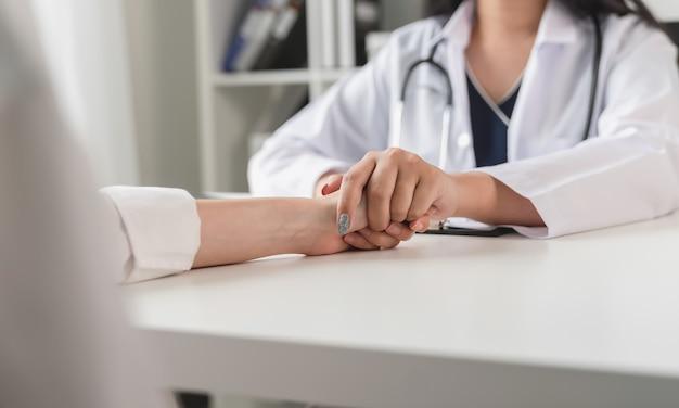 De dokter houdt handen vast om de patiënt te troosten en aan te moedigen. Premium Foto