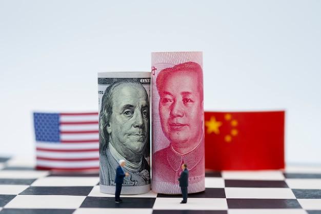 De dollar van de vs en het bankbiljet van china yuan met vlaggen op schaaklijst. het is een symbool voor de oorlogscrisis in de tariefhandel Premium Foto