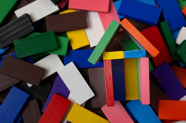 De domino-multikleur bouwt thuis op houten tafel. Premium Foto