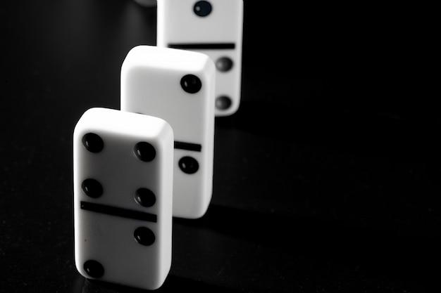 De dominostukken zetten op een rij op zwarte achtergrond Premium Foto