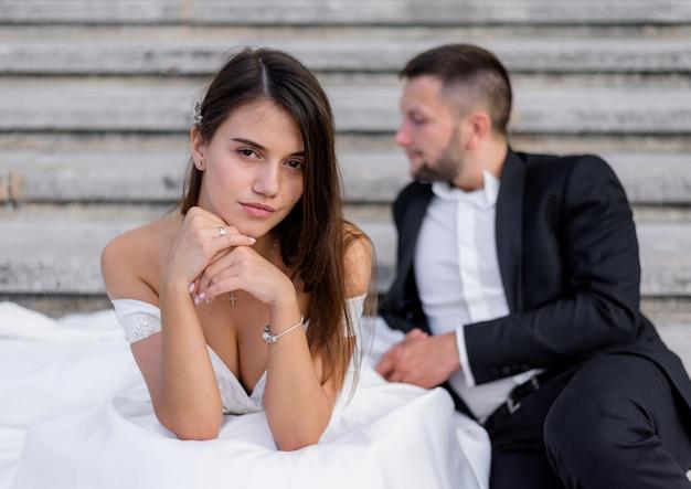 De donkerbruine bruid met grote borsten kijkt recht en een bruidegom zit op de achtergrond Gratis Foto