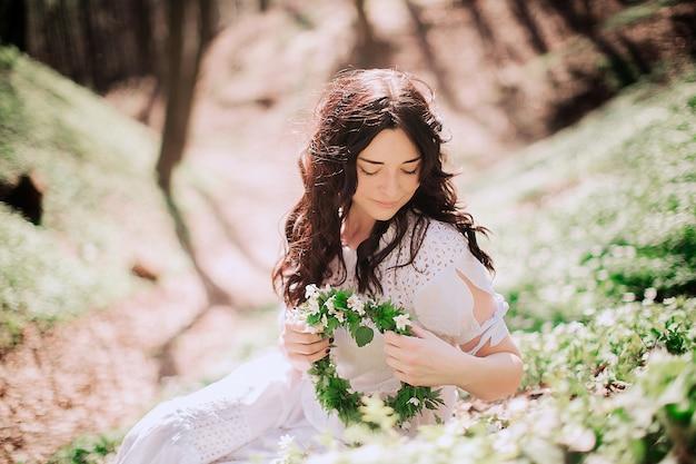 De donkerbruine dame bevestigt haar haarzitting op groen gras Gratis Foto