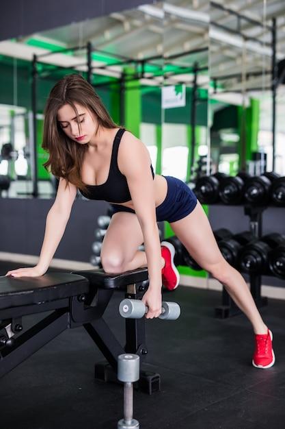 De donkerbruine vrouw met sterk geschikt lichaam doet verschillende oefeningen in moderne sportkleding Gratis Foto