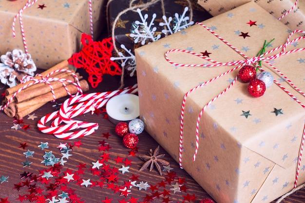 De doos van de de vakantiegift van kerstmis op verfraaide feestelijke lijst met het kaneelnoten van de denneappelskaneel en fonkelt sterren op houten achtergrond Gratis Foto