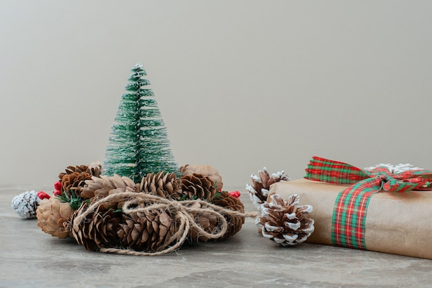 De doos van de gift van kerstmis, dennenappels en krans op marmeren tafel. Gratis Foto