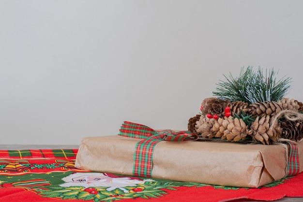 De doos van de gift van kerstmis en krans met dennenappel op marmer. Gratis Foto