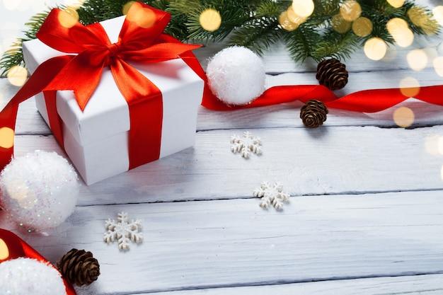 De doos van de gift van kerstmis met decoratie op witte houten tafel Premium Foto