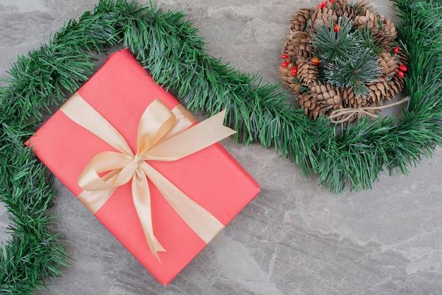 De doos van de gift van kerstmis, tak en krans op marmer. Gratis Foto