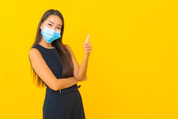 De draagmasker van het portret mooi jong aziatisch bedrijfsvrouw voor beschermt covid19 op gele achtergrond Gratis Foto