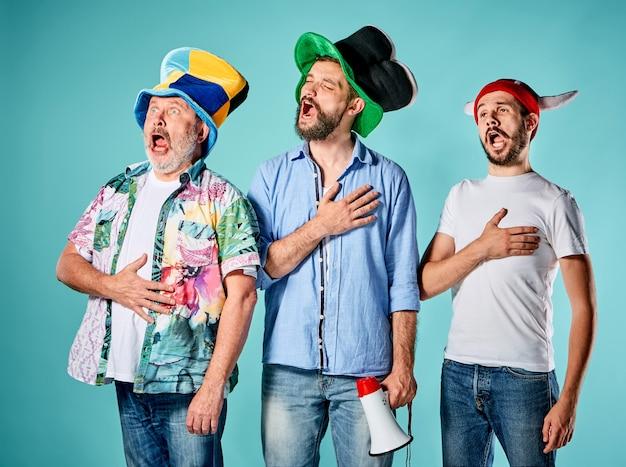 De drie voetbalfans zingen het volkslied over blauw Gratis Foto