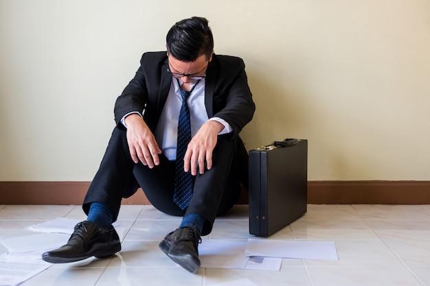 De droevige aziatische zakenman zit op vloer Premium Foto