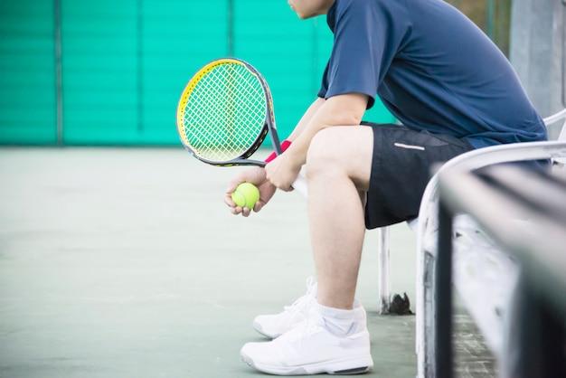 De droevige tennisspeler die in het hof zit na verliest een gelijke Gratis Foto