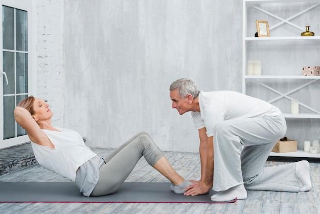 De echtgenoot die zijn vrouw met yoga helpen stelt op oefeningsmat Gratis Foto