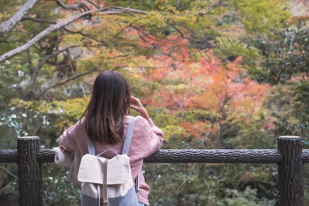 De eenzame vrouw die zich gelet op verzonken bevinden en bladeren bekijken verandert kleur in de herfst Premium Foto