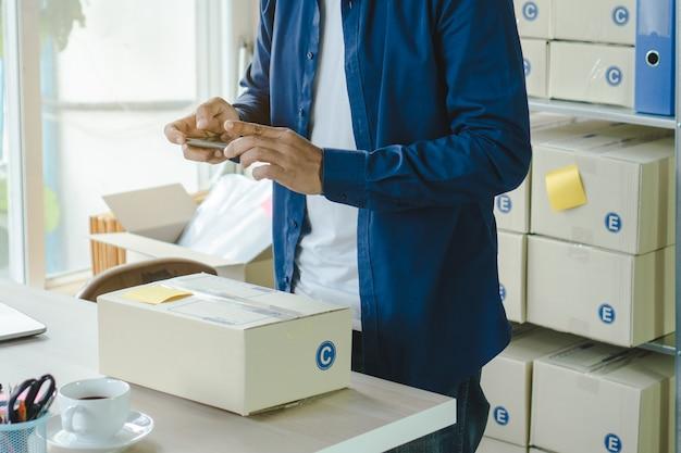 De eigenaar van een e-commercebedrijf neemt een foto van goederen die via een sociaal netwerk naar de klant worden gestuurd. Premium Foto