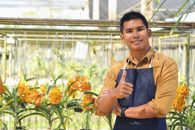 De eigenaar van het bedrijf orchid garden is blij met zijn succes na het ontvangen van de lening om het bedrijf uit te breiden. Premium Foto