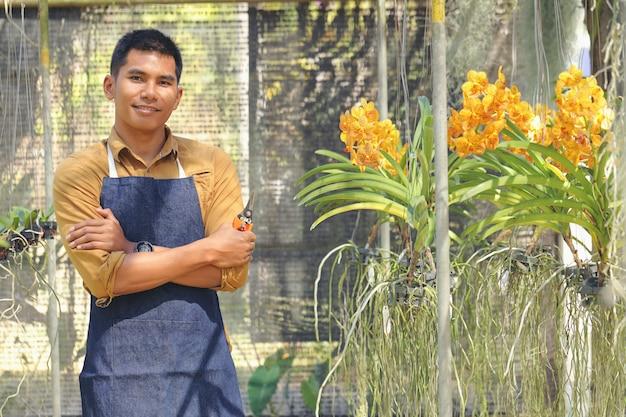De eigenaar van het orchid garden-bedrijf is blij met zijn succes na ontvangst van de investering. Premium Foto