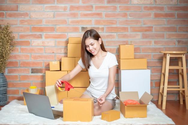 De eigenaar van het vrouwelijke ondernemer mkb-bedrijf controleert de bestelling met telefoon, laptop en verpakkingsdoos om haar klant te sturen Premium Foto