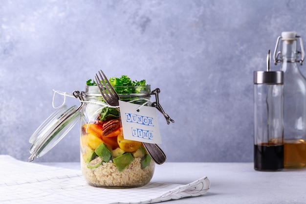 De eigengemaakte salade in glaskruik met quinoa en groenten met etiketlunchtijd geen plastiek en haalt concept weg Premium Foto
