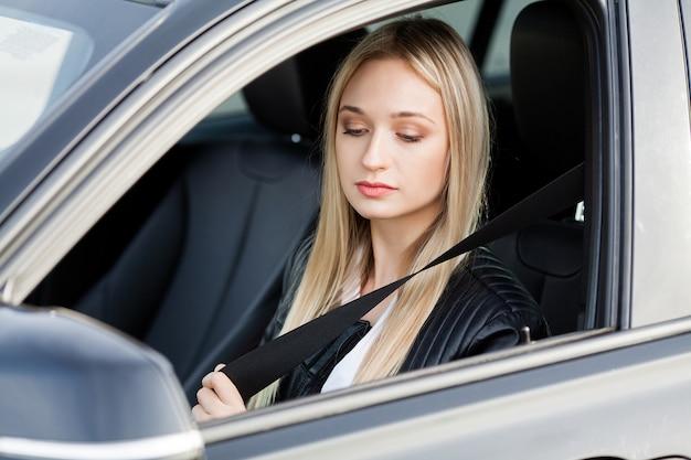 De elegante bedrijfsvrouw kleedde zich in het kostuum dat de veilige riem vastmaakt alvorens zijn auto te drijven Premium Foto