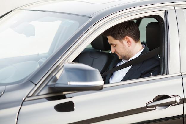 De elegante zakenman kleedde zich in het kostuum dat de veilige riem vastmaakt alvorens zijn auto te drijven Premium Foto