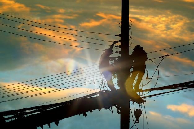 De elektricien die van silhouetmensen hoog op hemel werken. Premium Foto