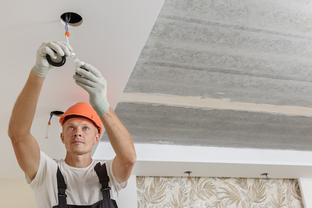 De elektricien installeert led-spots aan het plafond. Premium Foto