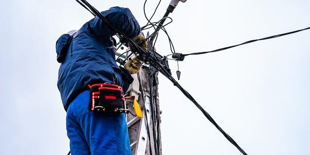 De elektricien vysotnik maakt de installatie van stroomnetten Premium Foto