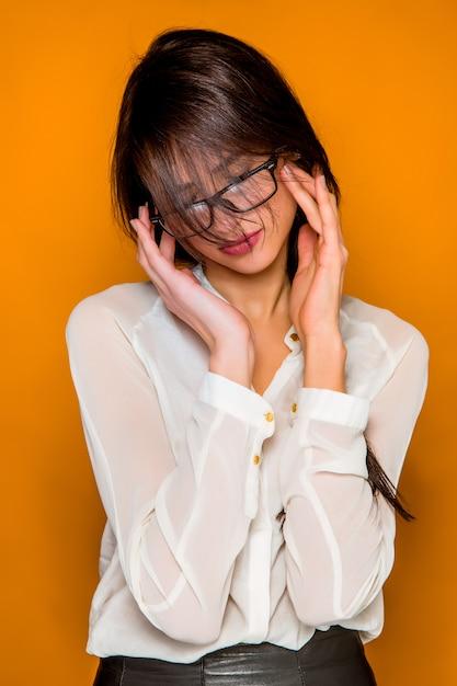 De ernstige gefrustreerd jonge mooie zakenvrouw op oranje muur Gratis Foto