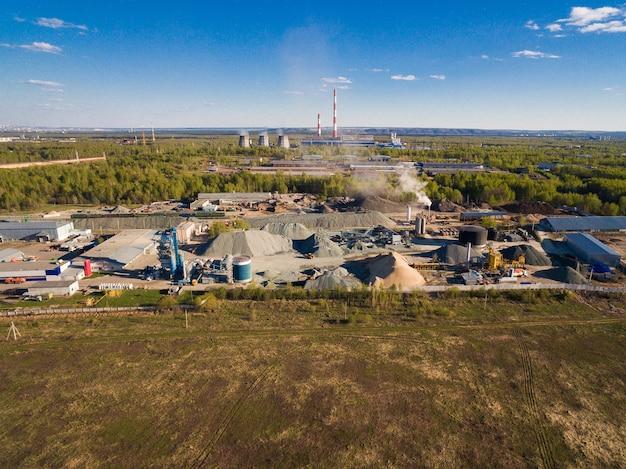 De fabriek ligt tussen bossen en velden, achter hem bevinden zich verschillende fabrieken en een elektriciteitscentrale. de fabriek dient de behoeften van wegenbouw Premium Foto