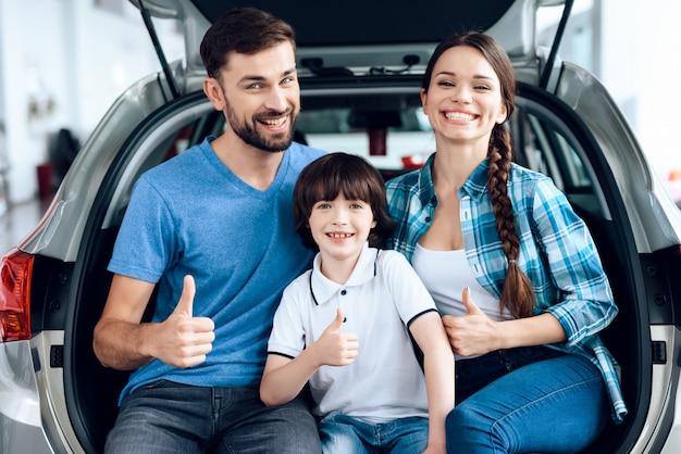 De familie is blij dat ze een nieuwe auto hebben gekocht. Premium Foto