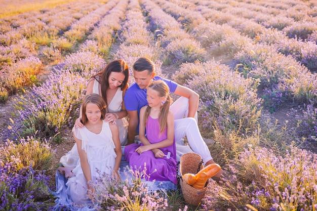De familie op lavendel bloeit gebied bij zonsondergang in witte kleding en hoed Premium Foto