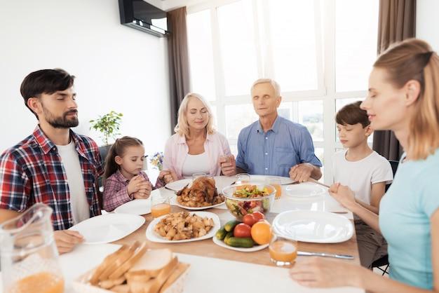 De familie zit aan de tafel voor thanksgiving Premium Foto