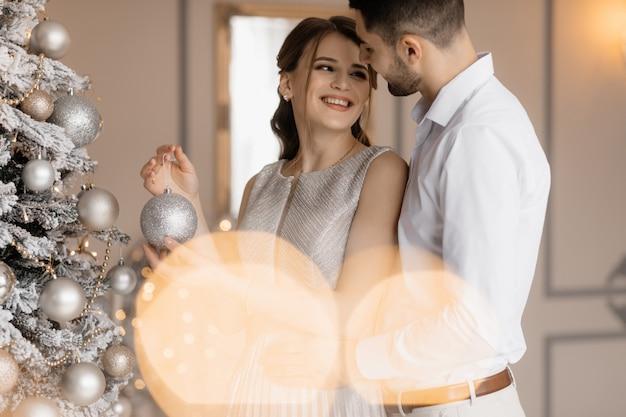 De fancy geklede man en de vrouw in zilveren toga omhelzen elkaar teder die zich vóór een kerstboom bevinden Gratis Foto